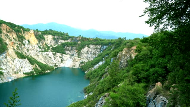 rock mountian with green lake and blue sky - chonburi province stock videos & royalty-free footage