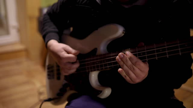 rock music artist, playing the bass guitar while recording his new song, in cozy and well equipped music studio - modern rock stock videos & royalty-free footage
