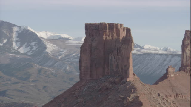 Rock pillars tower over a vast valley in Utah. Available in HD.