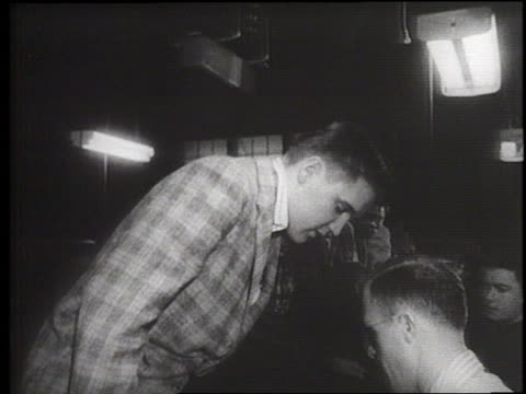 stockvideo's en b-roll-footage met rock singer elvis presley changes from street clothes to army issue as he enters the military in 1958 - army
