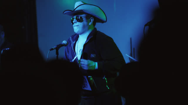 rock star dressed like a cowboy performs for an excited crowd at a popular music festival - beatnik stock videos & royalty-free footage