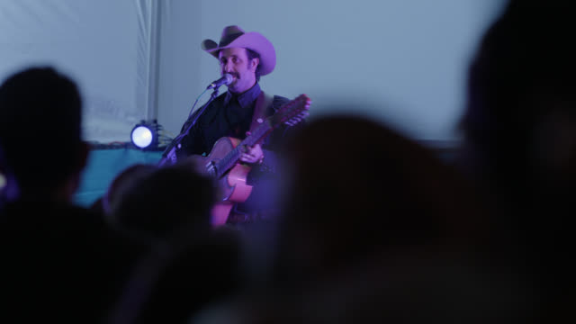 rock star dressed like a cowboy sings and plays the guitar for an excited crowd at a popular music festival - beatnik stock videos & royalty-free footage