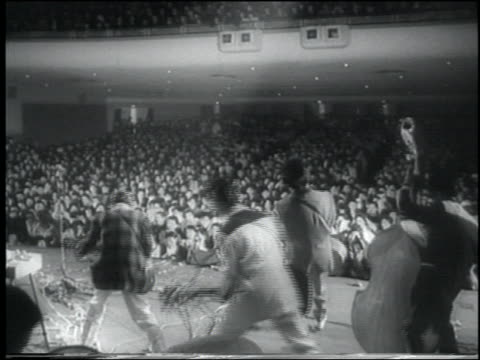 b/w 1958 newsreel rear view rockabilly band on stage before large crowd at concert / tokyo - klassischer rock and roll stock-videos und b-roll-filmmaterial