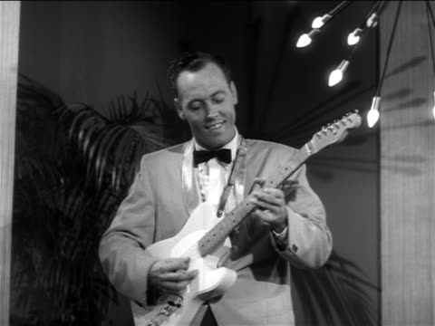 b/w 1956 rockabilly guitar player (from johnny burnette's band) soloing on small stage / feature - klassischer rock and roll stock-videos und b-roll-filmmaterial