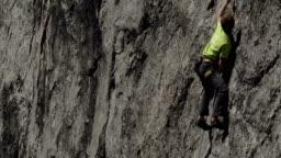Rockclimber climbing limestone cliff