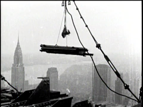 rockefeller center is shown from above and below / cranes raise materials to the top / men work at the top of the building / men are raised higher... - rockefeller center video stock e b–roll