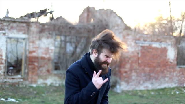 stockvideo's en b-roll-footage met rocker having fun and listening to music outdoors - confrontatie