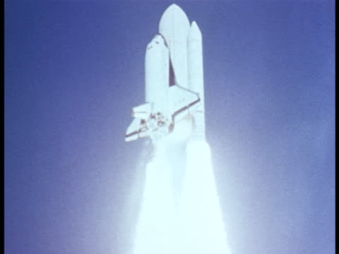 A NASA rocket carries a space shuttle into space.