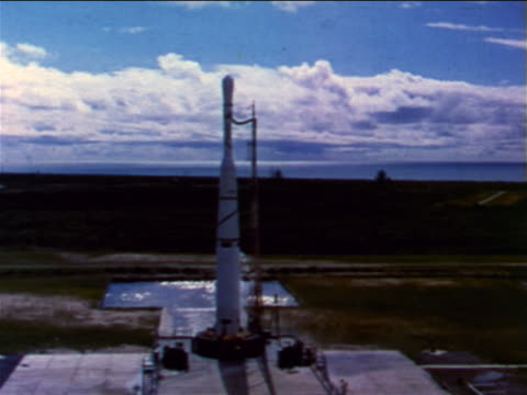 1960 rocket carrying satellite blasting off from launch pad / industrial - 1960 stock-videos und b-roll-filmmaterial