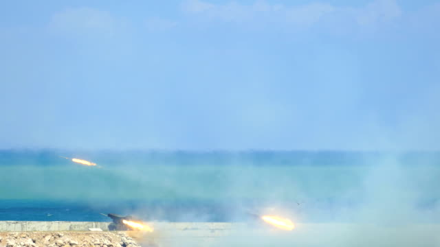 rocket launchers firing at the coast - artiglieria video stock e b–roll