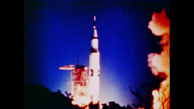 a rocket launches at night the earth viewed from beneath its rocket boosters - anno 1969 video stock e b–roll