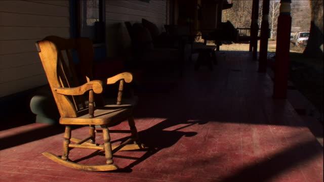 vídeos y material grabado en eventos de stock de a rocking chair occupies a shady porch. - mecedora