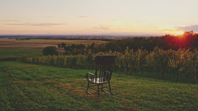 rocking chair rocking in lawn overlooking idyllic rural sunset landscape, real time - dondolarsi video stock e b–roll