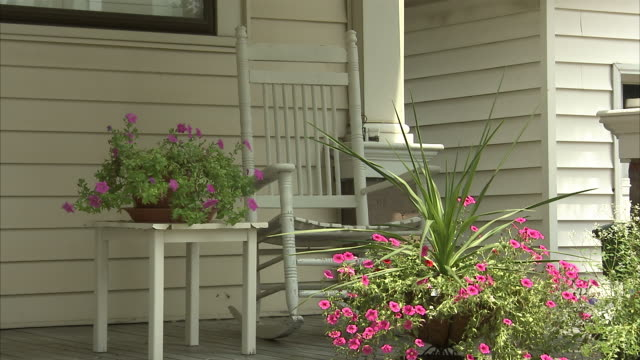 a rocking chair sits empty on a decorated porch. - rocking chair stock videos & royalty-free footage