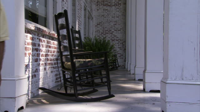 stockvideo's en b-roll-footage met rocking chairs on concrete floor porch of whitewashed brick building w/ pillars fern in stand bg fg chair rocking slightly no people relaxed... - schommelstoel