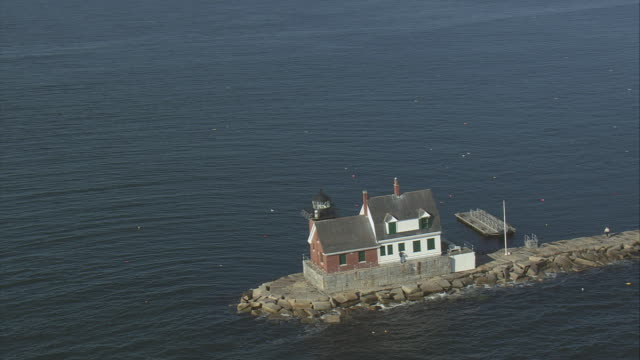 aerial rockland harbor breakwater lighthouse, causeway, and motorboat cruising on calm waters / rockland, maine, united states - kryssa bildbanksvideor och videomaterial från bakom kulisserna