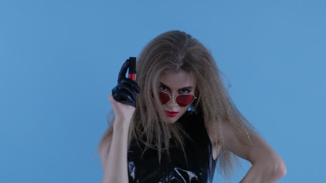 rock`n`roll-like fashion model holds red lipstick in her hand. fashion video. - red lipstick stock videos & royalty-free footage