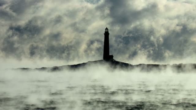 rockport's thacher island lighthouse in arctic sea smoke - lighthouse stock videos & royalty-free footage