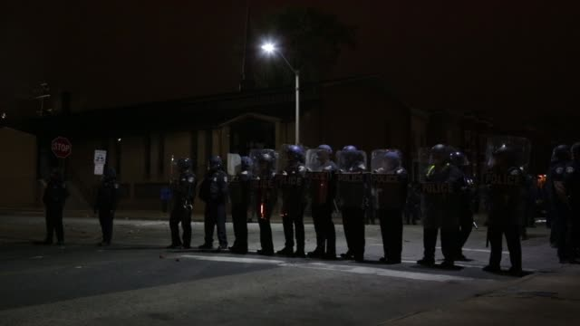 vidéos et rushes de rocks and other debris are seen on the street behind a riot police line near the western district police station in the late night hours baltimore... - maryland état