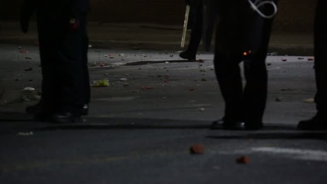 Rocks and other debris are seen on the street behind a riot police line near the Western District Police Station in the late night hours Baltimore...