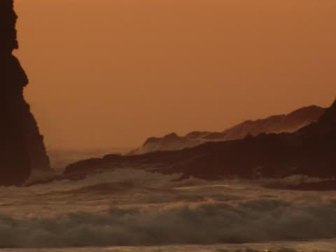 vídeos y material grabado en eventos de stock de rocks and surf at sunset - artbeats
