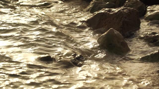 vídeos de stock, filmes e b-roll de rocks and water at sunset - pedra rocha