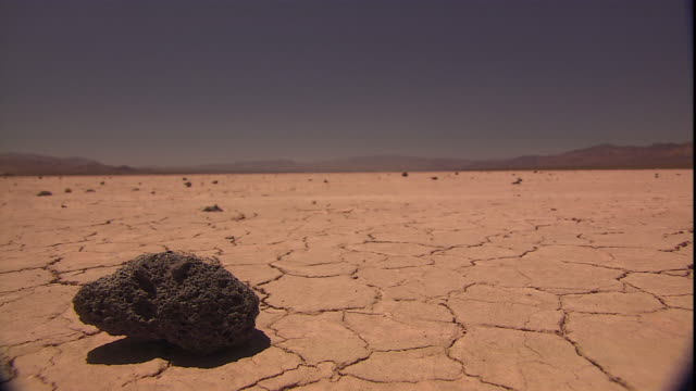 rocks are scattered on a cracked desert landscape. - land stock videos & royalty-free footage