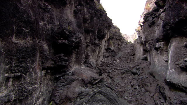 rocks, boulders and burnt debris line a crevice near a volcano. - crevice stock videos & royalty-free footage