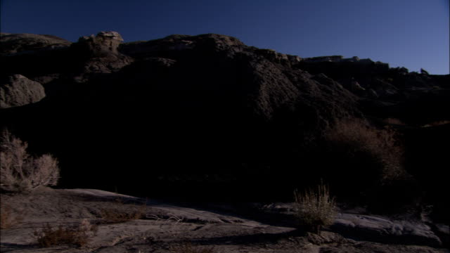 rocks cover the hillsides of the bisti badlands in new mexico. - bisti badlands stock videos & royalty-free footage