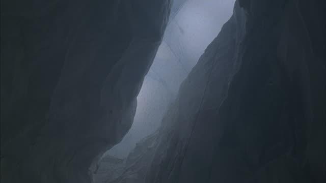 Rocks fall around a climber who slides and falls.