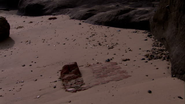 Rocks litter a severely eroded beach along England's coast. Available in HD.