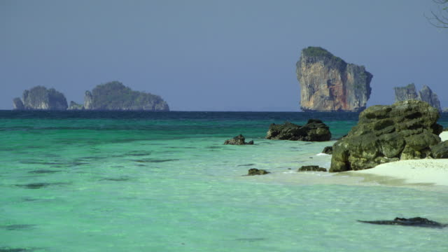 ws rocks on beach, limestone pinnacles in distance, krabi, thailand - see other clips from this shoot 1459 stock videos and b-roll footage