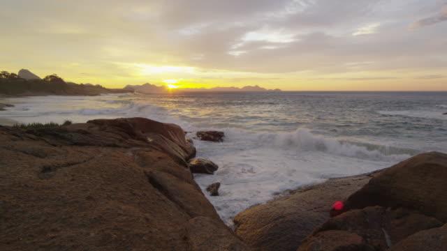 Rocks reaching into ocean at sunset