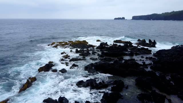 Rocks Strewn on Beach Below Flying Drone on Rough Day