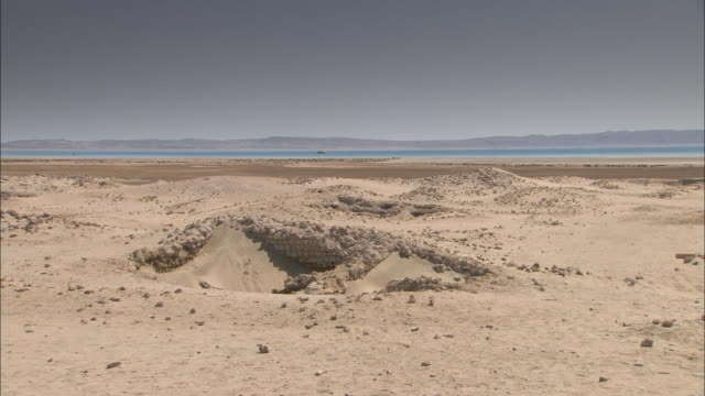 rocks surround a small sand dune near the river nile in luxor, egypt. - küste stock-videos und b-roll-filmmaterial