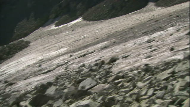 rocks surround a snow patch in japan's tateyama mountain range. - steep stock videos and b-roll footage