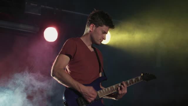 vídeos de stock, filmes e b-roll de rockstar playing electric guitar on stage during gig - guitarist