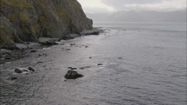 vídeos de stock e filmes b-roll de a rocky alaskan coast borders dutch harbor. - alasca