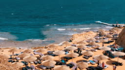 Rocky Beach in a Bay with Umbrellas and Sunbeds in Egypt on Red Sea