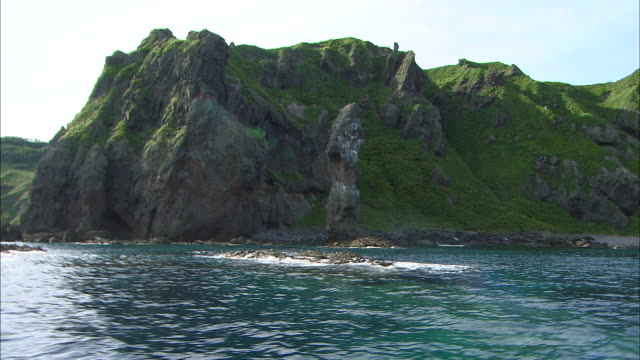 Rocky cliff coast at foot of Cape Kamui Wide and Long Shot Dolly Shot from aboard A tunnel is seen beneath the cliff