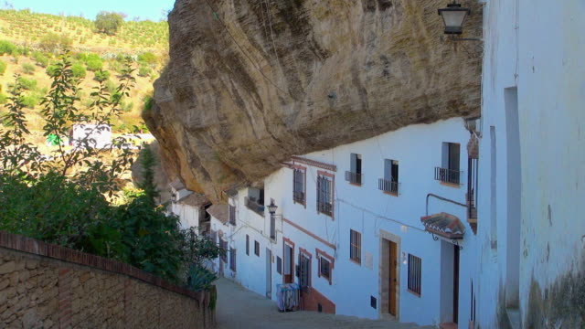 Rocky Cliff Overhanging White Apartment Buildings