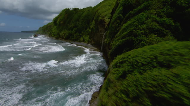 Rocky cliffs of Rosalie Bay and the Wavine Cyrique waterfall on the Caribbean Island of Dominica.