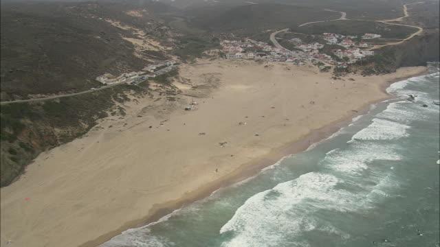 aerial ws rocky coast and small town on edge / aljezur, faro, portugal - algarve stock-videos und b-roll-filmmaterial