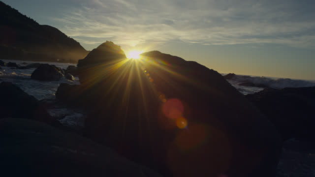 rocky coast at sunset, new zealand - sunbeam stock videos & royalty-free footage