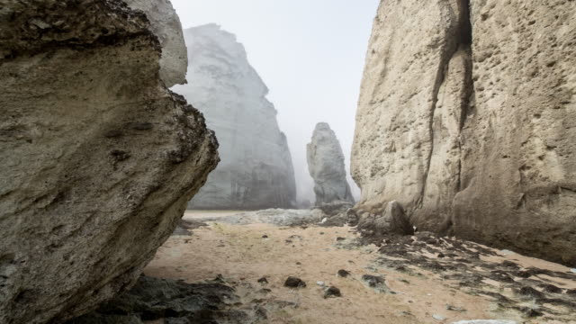 vidéos et rushes de rocky coast washed by fog early in the morning 1 - exposé aux intempéries