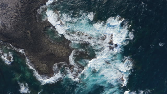 rocky coastline contrasts. foamy waves and turquoise wateraerial view - high contrast stock videos & royalty-free footage