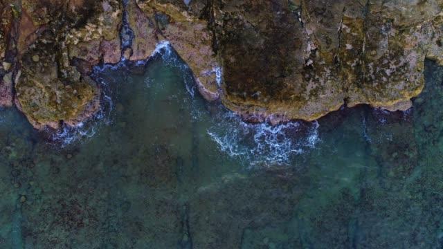 vídeos de stock e filmes b-roll de rocky coastline from directly above - penhasco caraterísticas do território