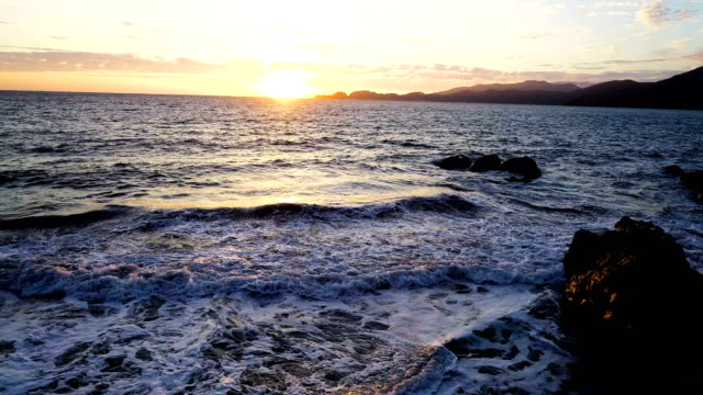 slow motion: rocky coastline sunset on pacific coast baker's beach of san francisco , california , usa - northern california stock videos & royalty-free footage