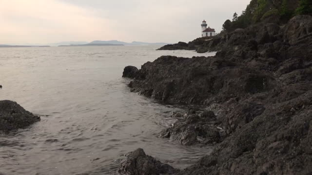 Rocky Coastline with Lighthouse and Sunset