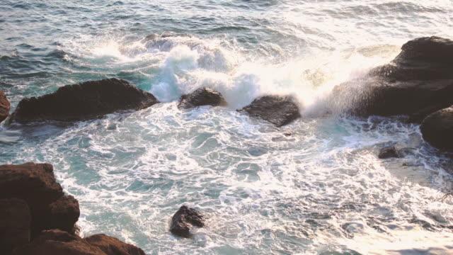 vídeos de stock, filmes e b-roll de litoral rochoso com ondas - pedra solta